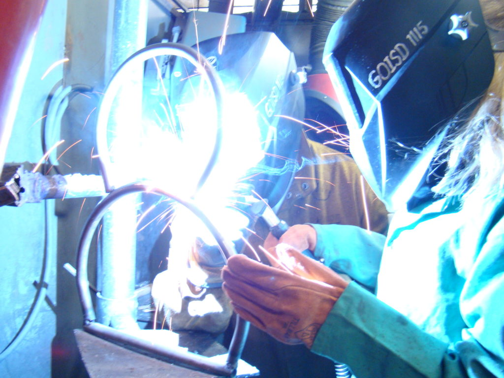 Students welding some curved metal together.